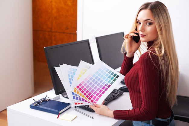 Портрет счастливой молодой коммерсантки сидя на столе пока работающ