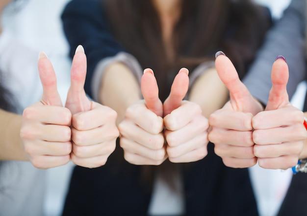Бизнес команда показывает палец вверх в офисе