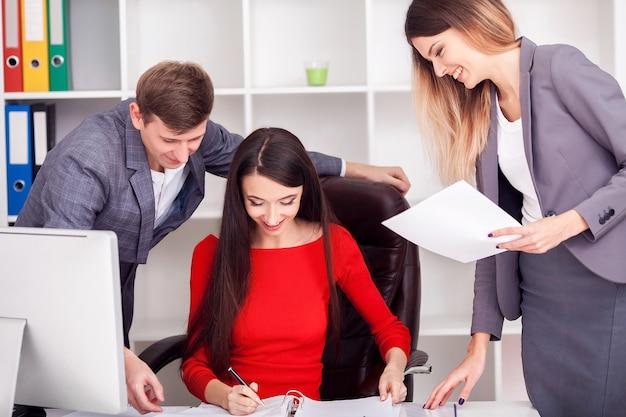若いビジネスチームがオフィスの仕事机の上に付箋を読みます。