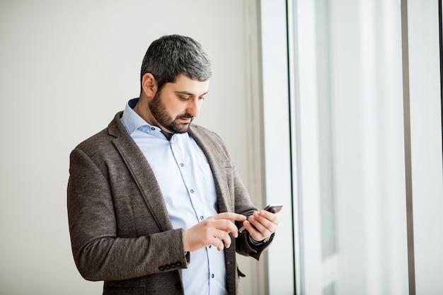Мобильный телефон вскользь городского профессионального бизнесмена отправляя смс счастливый внутри офиса