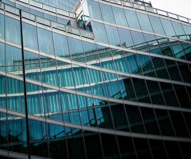 青い曇り空の上の現代ガラス建築高層ビルの織り目加工の背景に視点と下側の角度のビュー