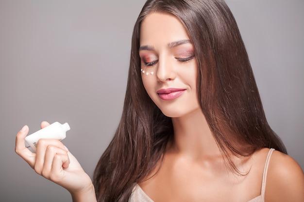 女性の顔のスキンケア。目の前でクリームを適用し、ボトルを保持している魅力的な若い女性の肖像画。ナチュラルメイクと新鮮な肌を持つ微笑んでいる女の子のクローズアップ。美容化粧品高解像度