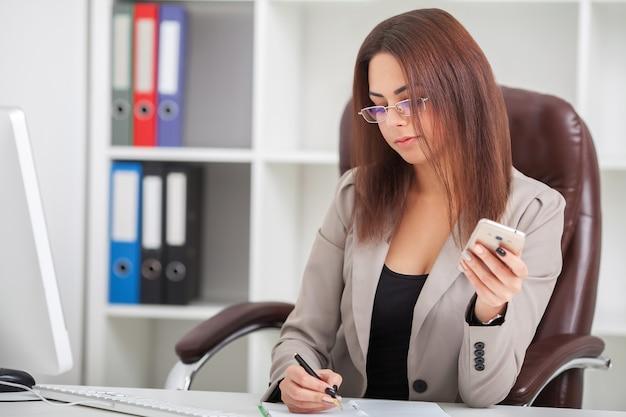 いくつかの文書を通過する彼女の仕事机に座っている美しい若い女性のショット。