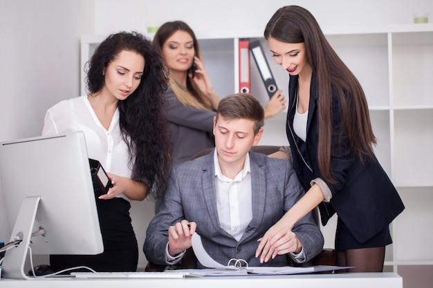 Команда молодых креативных менеджеров, работающих с новым проектом запуска в современном офисе.