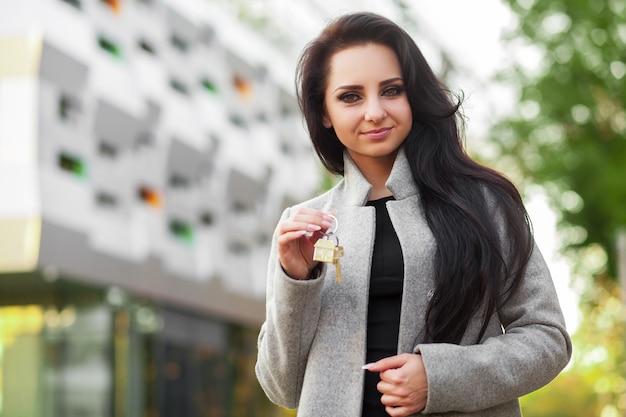 モダンな住宅街に屋外に立っている若い女性の全米リアルター協会加入者または実業家の肖像画
