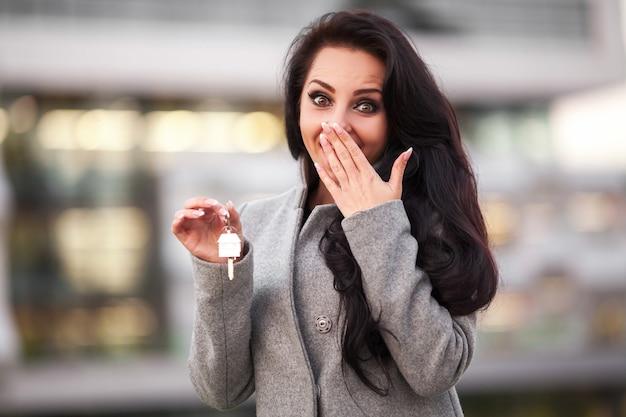 Улыбающаяся деловая женщина с ключами над офисной комнатой или новой квартирой