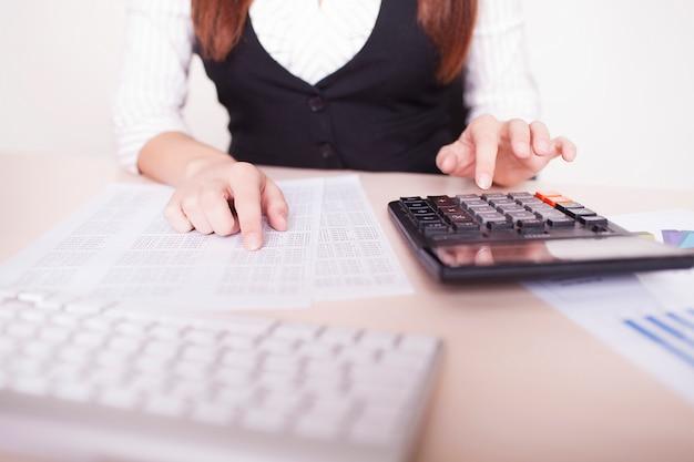 Деловая женщина в офисе сидит за столом и работает