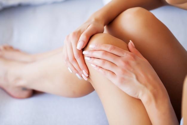 Боль в колене, несчастная женщина, страдающая от боли в ноге дома