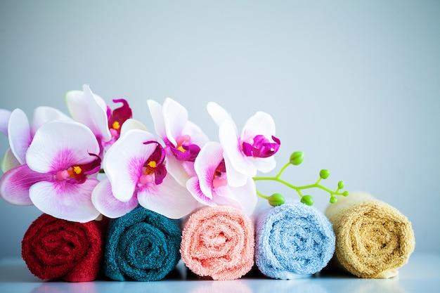 色付きのタオルとバスルームのコピースペースを持つ白いテーブルの上の蘭