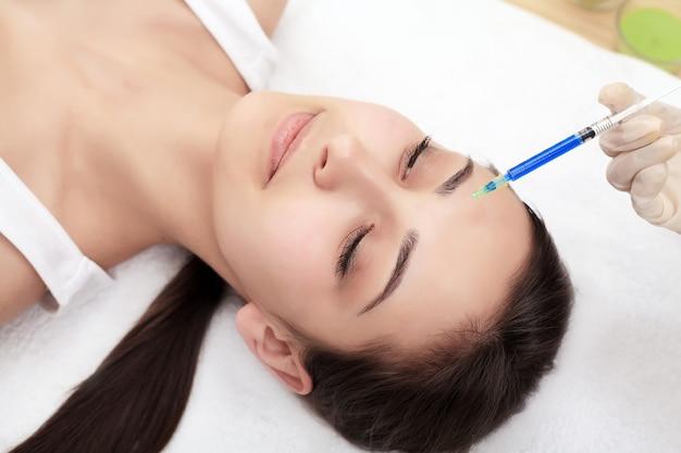 美容注射、女性の顔の近くに注射器で医師の手のクローズアップ