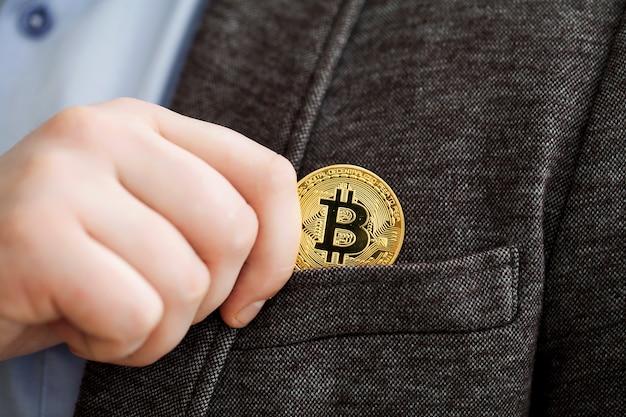 Бизнесмен, удаляющий или кладущий золотой биткойн в карман