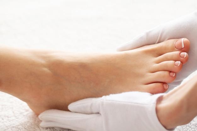 女性のフレンチペディキュア。長い脚、柔らかい肌に触れる女性の手を閉じます。脱毛