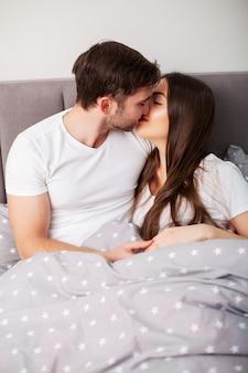 幸せなカップルがベッドの中で楽しんで。お互いを楽しんで寝室で親密な官能的な若いカップル