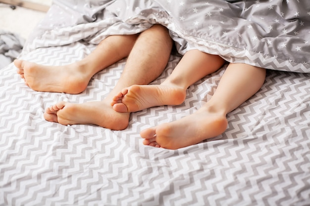 毛布の下の恋人の足。ベッドで楽しんで幸せなカップル