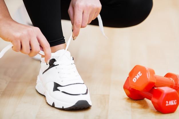 フィットネス。女性ランナー締め付け靴ひも。靴のクローズアップで走っているランナー女性足