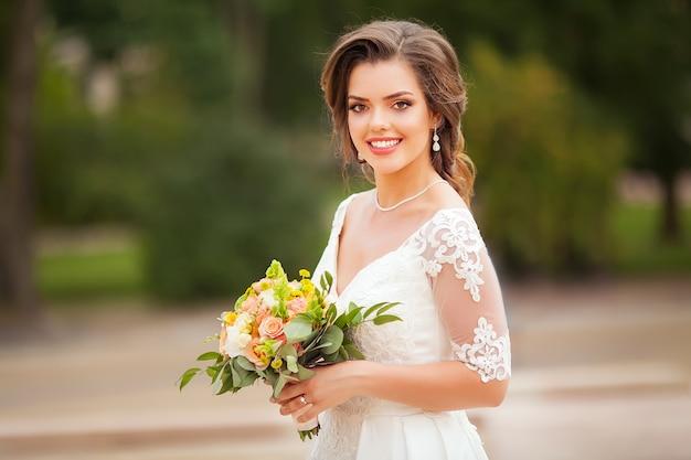 花を持つ若い美しい魅力的な花嫁の肖像画