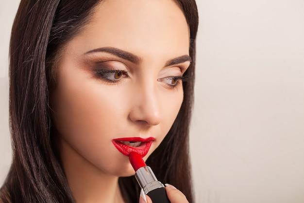 美しい女性は口紅で唇を塗料します。