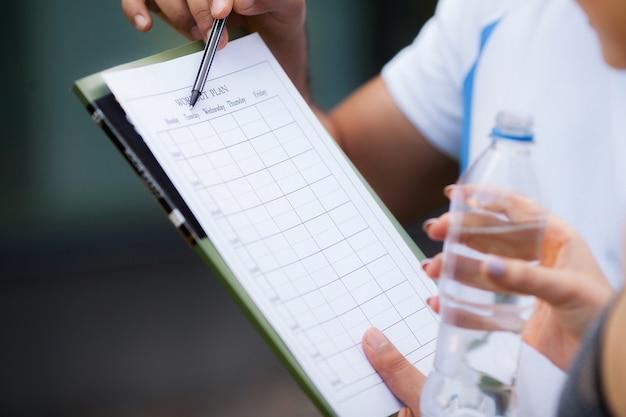 Фитнес план. спортивный тренер составляет план тренировки крупным планом