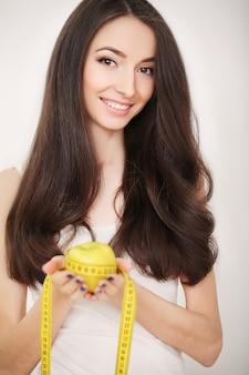 ダイエット、スリムな若い女性の巻尺で腰を測定