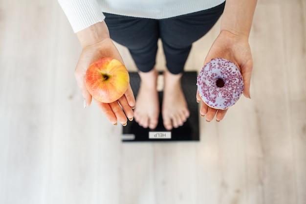 ダイエット。ドーナツとリンゴを保持している体重計で体重を測定する女性。お菓子は不健康なジャンクフードです。ダイエット、健康的な食事、ライフスタイル。減量。肥満。上面図