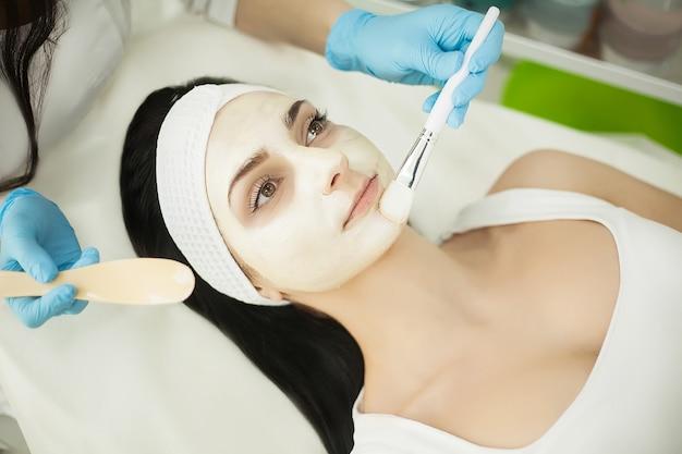 顔のマスクが彼女の顔に適用されている間健康スパのマッサージテーブルに横たわる女