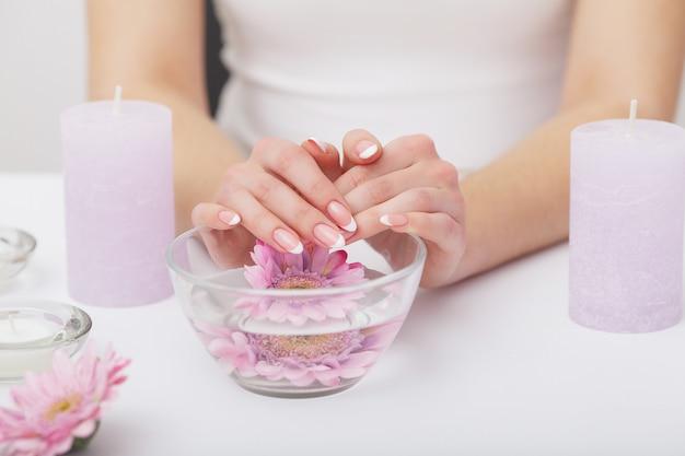 美しいフランスのマニキュアの爪を持つ女性の手