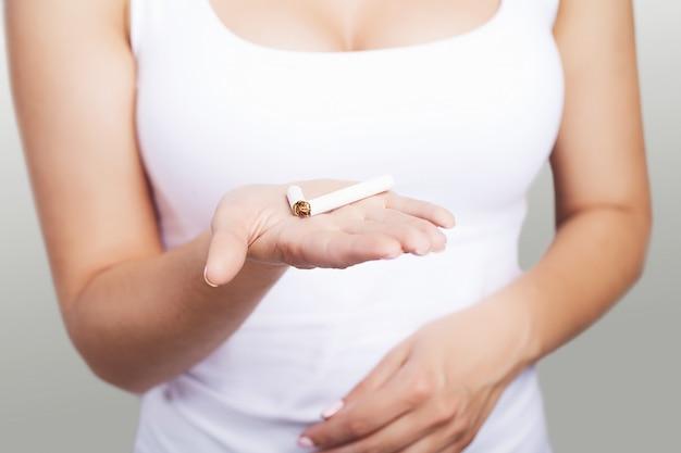 禁煙、壊れたタバコを持つ女性の手のクローズアップ