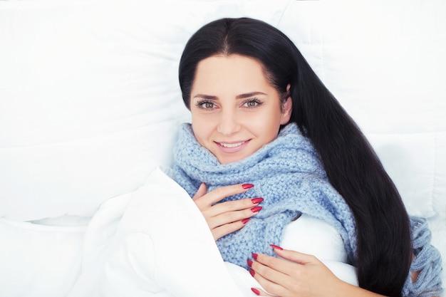 横になっている美しい女性と雪のベッドで寝る