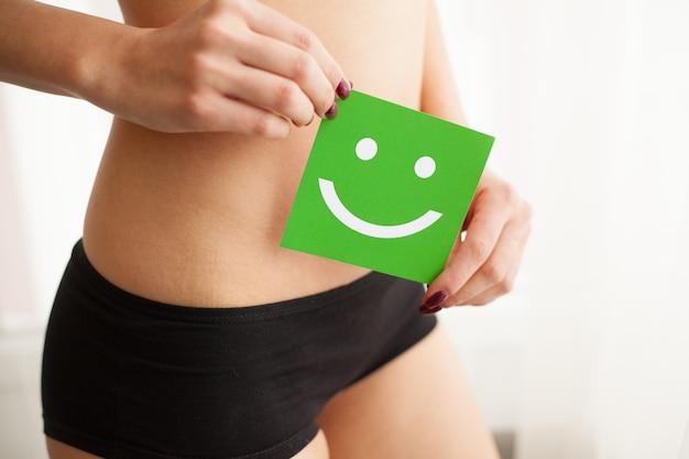 女性の健康笑顔のカードを持つパンティーで美しい女性の身体