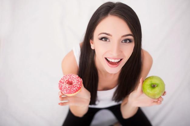 Концепция диеты, молодая женщина, выбирая между фруктами и сладостями
