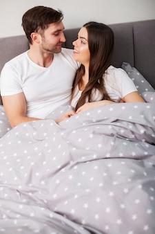 ベッドで楽しんで幸せなカップル。お互い楽しんで寝室で親密な官能的な若いカップル
