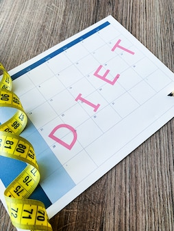 План диеты. измеряя лента и план диеты на деревянной предпосылке.