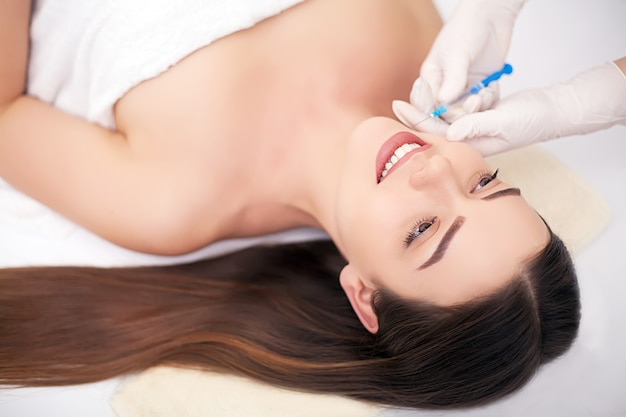 美容治療として唇に注射を持つ女性
