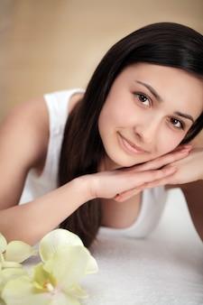 Красивая молодая женщина с чистой свежей кожей прикосновения собственного лица, уход за лицом, косметология, красота и спа,
