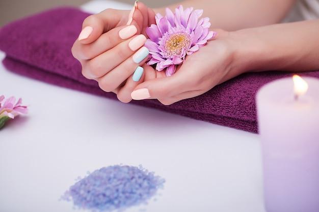 ネイルケア。ビューティーサロンで自然な爪と美しい女性の手のクローズアップ。