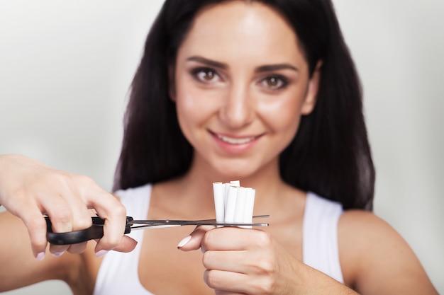 Бросить курить. макрофотография женских рук, проведение кучу сигарет и резки их пополам с ножницами.