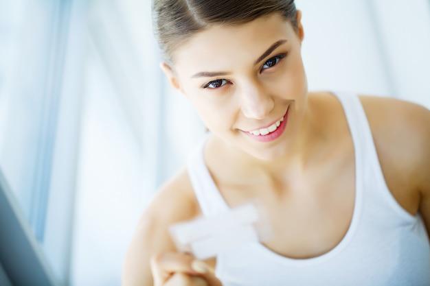 歯のホワイトニング。ホワイトニングストリップを保持している美しい笑顔の女性。高解像度画像
