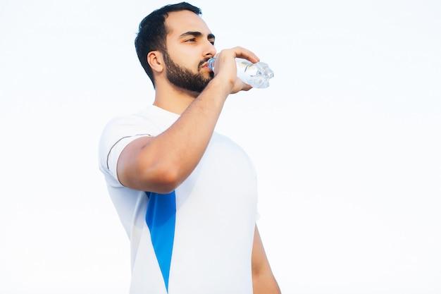 疲れたランナーの男は、トレーニングの後、公園で水を飲む