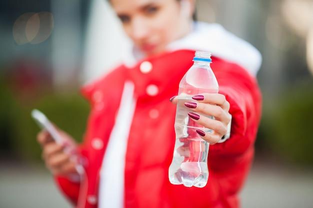 フィットネス女の子。水でボトルを保持しているスポーツ女性。大都市の健康的なライフスタイル。