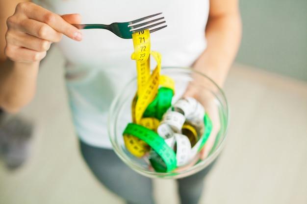 ダイエットと減量。女性は、ボウルとフォークを測定テープで保持します