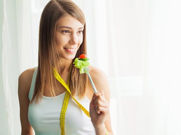 ダイエット。新鮮なサラダを食べて幸せな遊び心のある少女の肖像画
