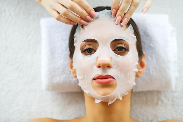 美しさフェイスマスクと美容院で美しい女性。マッサージ台の上に横たわる。ピュアでフレッシュな肌。スキンケア。高解像度
