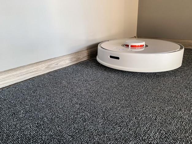 スマートハウス掃除機ロボットは居間の床の上を走ります。