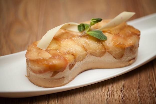 木製の背景に白い皿にミントとアップルパイ