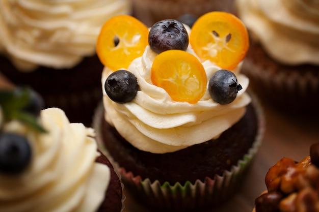 木製のテーブルの上の果実とおいしいカップケーキをクローズアップ