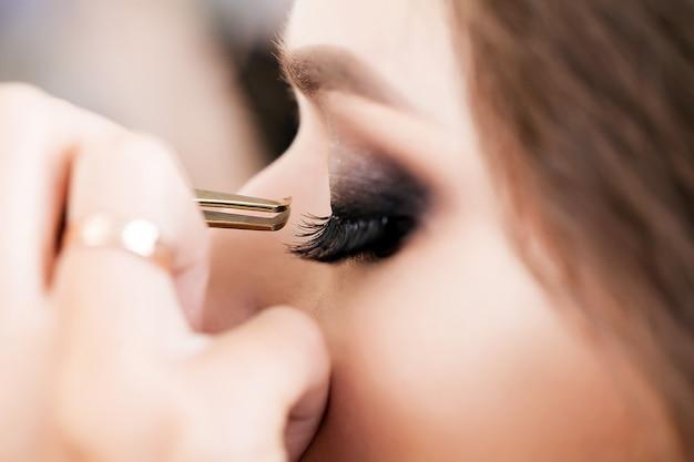 Молодая, красивая девушка наносит макияж в салоне красоты