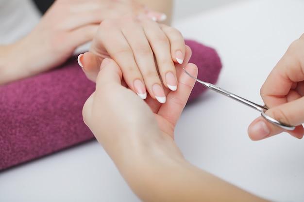 女性はマニキュアの手順を受けるネイルサロンで手します。