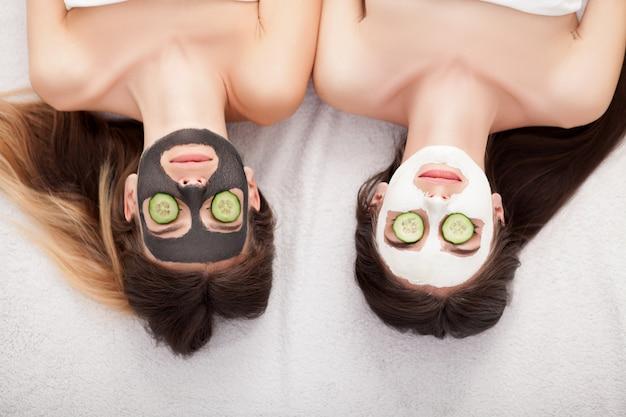 スパ。彼女の手で顔のマスクとキュウリのスライスを持つ女性