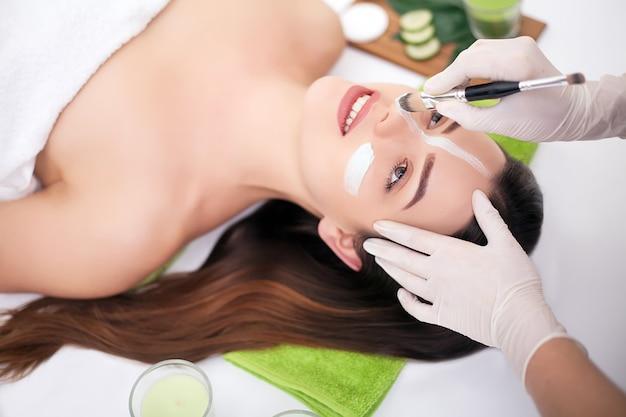Спа . рука, применяя питательную маску на женское лицо в спа салоне
