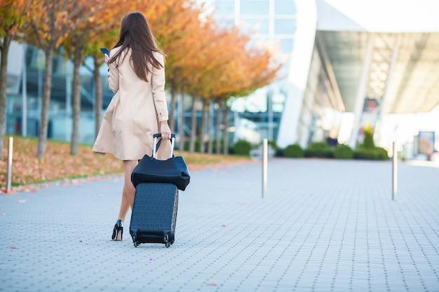 若いカジュアルな女性は飛行機で待っているスーツケースとウィンドウで空港に行きます